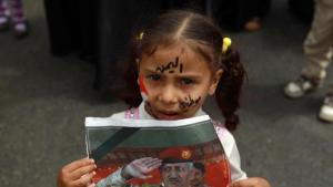 """""""הצערנו שאנו לובשים את מדי הצבא הזה"""": ילדה תימניה מעמראן מחזיקה את תמונתו של אל-קושייבי"""